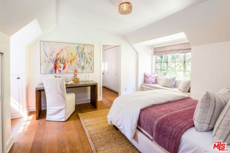 A lovely abstract canvas is mounted above the wooden desk in this guest bedroom with a white bed on a jute rug and a window seat nook accented by a pink chevron pillow.