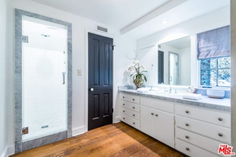 Beck & Marissa Ribisi's bathroom was designed with a long marble vanity cabinet and a sink. The shower area was separated with a glass door, walls were painted in white and flooring in wood parquet finish.