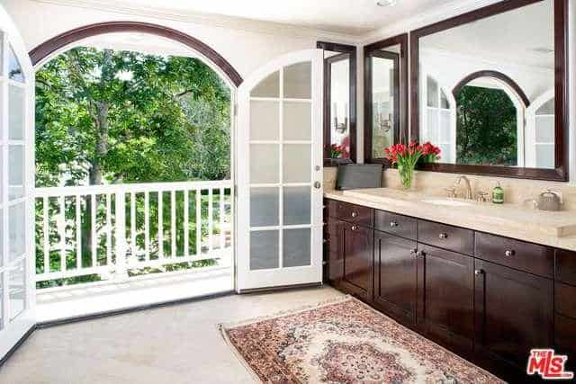 Large double doors connect the primary bathroom to the balcony.