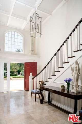 James Corden's all-white traditional foyer with 2-story coffered ceiling and pristine tile flooring.