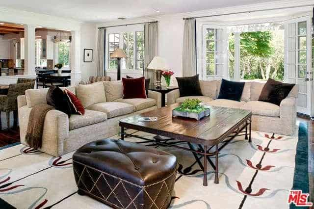 Neutral-colored furniture and a large patterned rug occupy the family room.