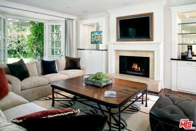 Dark velvet pillows lay on the beige sofas in this living room with a french door that opens to the lush green yard. It has a black leather ottoman and wooden coffee table facing the fireplace and television.