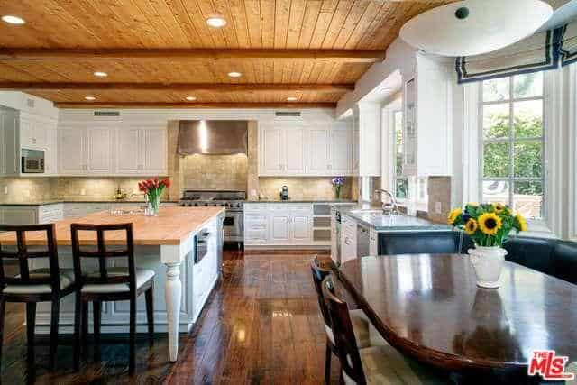 Wood beam ceiling complements the polished hardwood floor on this spacious kitchen. It has recessed lighting, center breakfast island and white cabinetry.