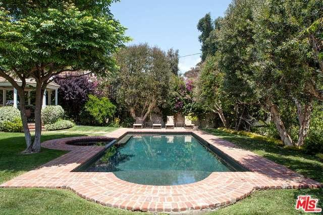 The Roman-Grecian style swimming pool with a hot tub has a brickwork surround while the surrounding trees provide privacy and some shade.