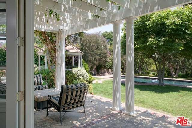 The covered porch looks out to the inviting outdoors including the gazebo and swimming pool.
