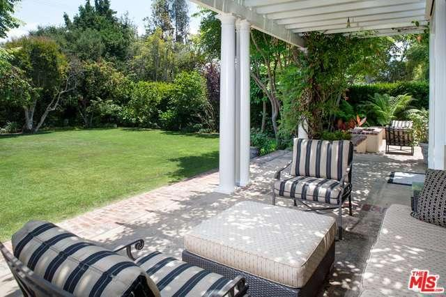 Behind the porch seating sits the open fire pit and a green gardenthat lends a natural privacy screen.