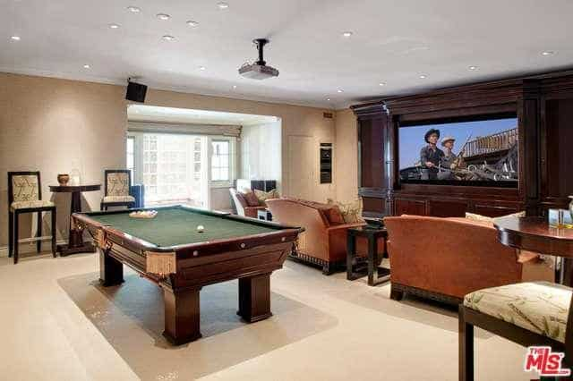 Recreational area with a huge television mounted on the wood paneled wall and a pool table that sits behind the coral sofas over beige carpet flooring.