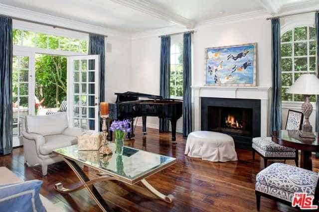 Large windows and floor-to-ceiling curtains add visual height to the formal living room while a grand piano beside the open fireplace add a touch of elegance.