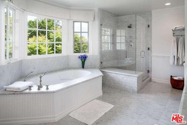 This bathroom with large bay windows, white marble tiles and beadboards achieves a light and airy effect.