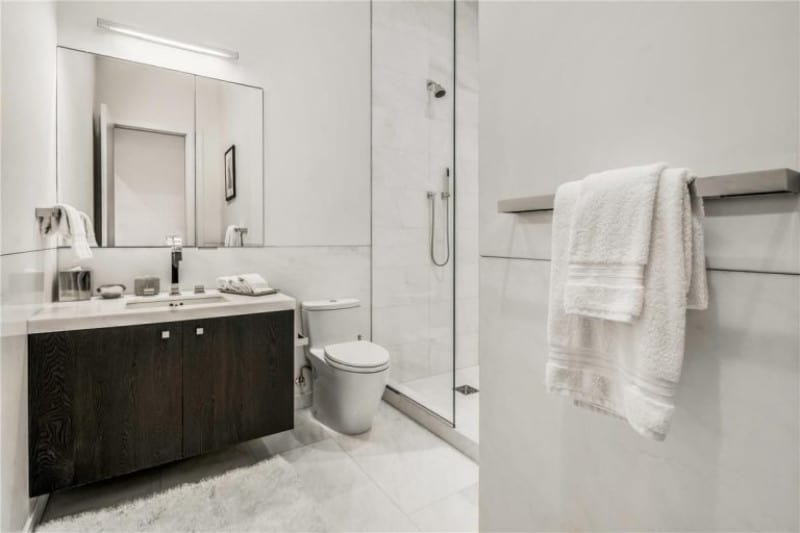 JLo's bathroom in white featuring wood laminated vanity cabinet with a large mirror, frameless glass shower door and ceramic tiles flooring with a carpet.