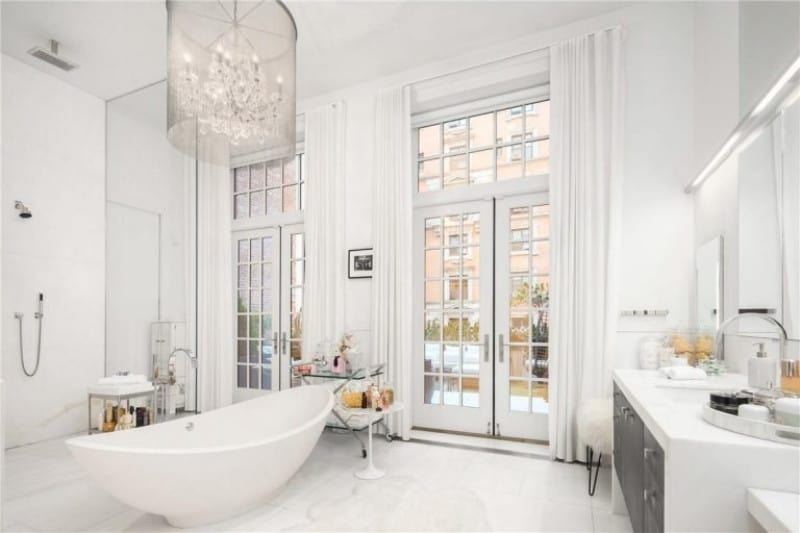 This master bathroom boasts a marvelous chandelier set on a high ceiling. The white walls and floors surround the whole room featuring a freestanding tub and an open shower.
