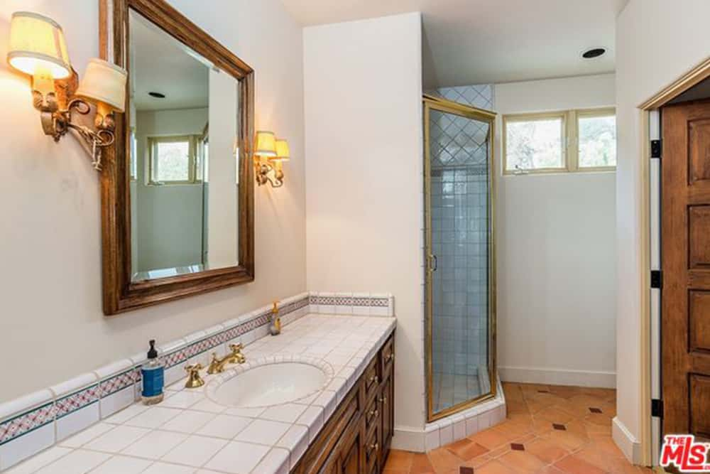 The guest bathroom features a single vanity sink and a corner bathroom cubicle.