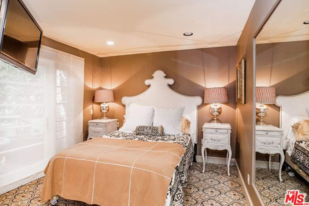The small guest bedroom has brown walls for visual warmth and a large mirror to add visual space.