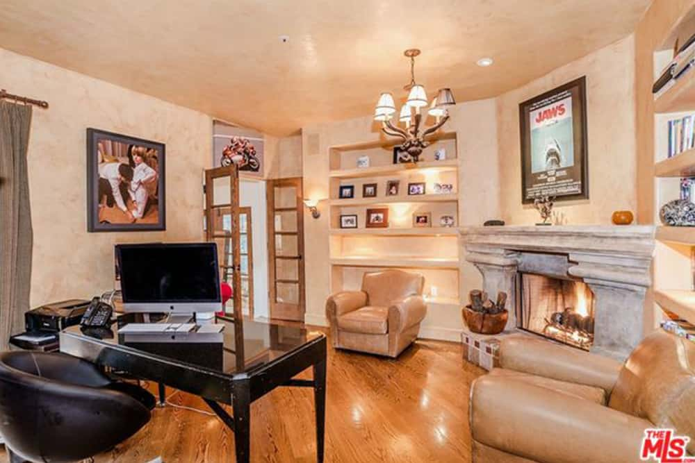 This home office offers a seating area by the fireplace in between built-in shelving. It has a black office desk and round back chair over hardwood flooring.