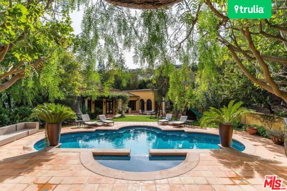 kendall jenners spacious outdoor area has a stunning swimming pool with waterfall and comes with a large stone patio which is perfect for entertaining - Outdoor House Pools