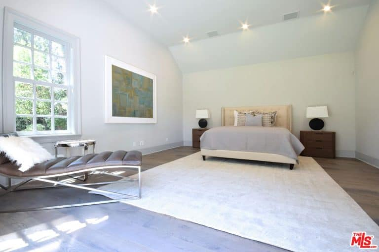 Spacious guest bedroom features a cream tufted bed on a beige rug and leather lounge chair accented with a faux fur pillow by the framed window.