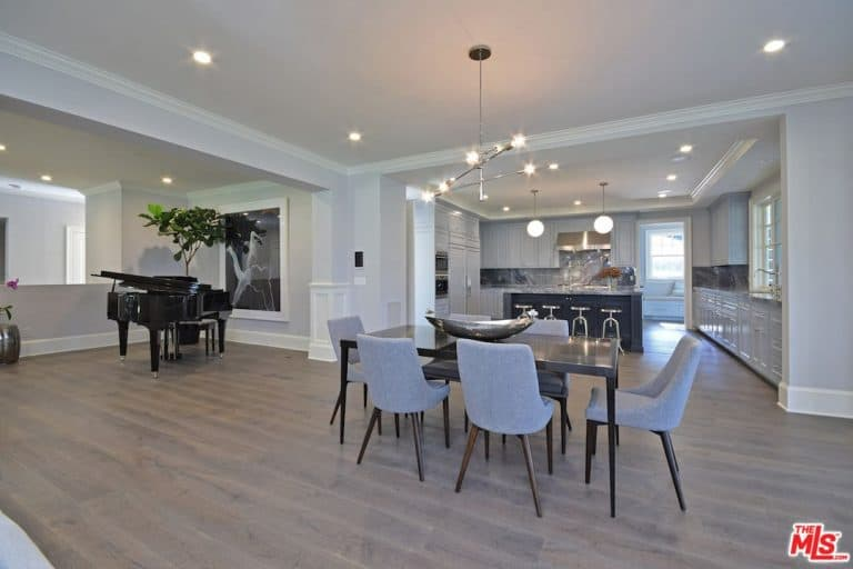 Spacious dining area showcasing a black dining table with a modern centerpiece paired with gray chairs. An industrial chandelier along with recessed lighting illuminated the room.