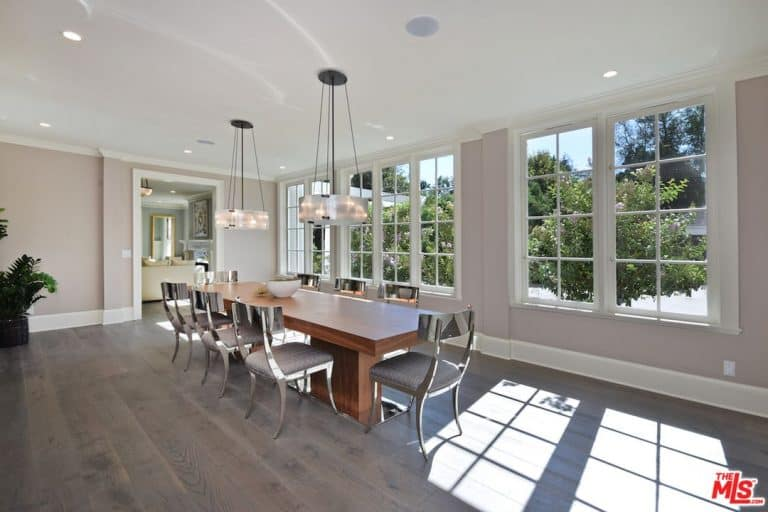 Dining room with white framed windows and hardwood flooring. It includes a wooden table with stylish chairs lighted by a pair of drum chandeliers.