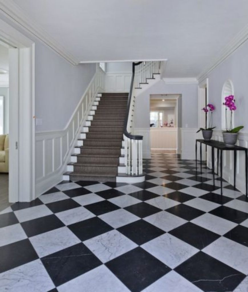 Kyle Richards And Mauricio Umansky's entryway's laminated classic black and white checkered flooring looks perfect and compliments the brown stairs that leads to the second floor.