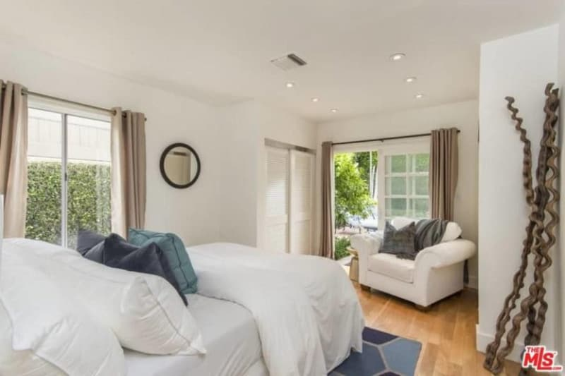 Small master bedroom boasting hardwood floors and white walls, along with a white ceiling lighted by recessed lights.