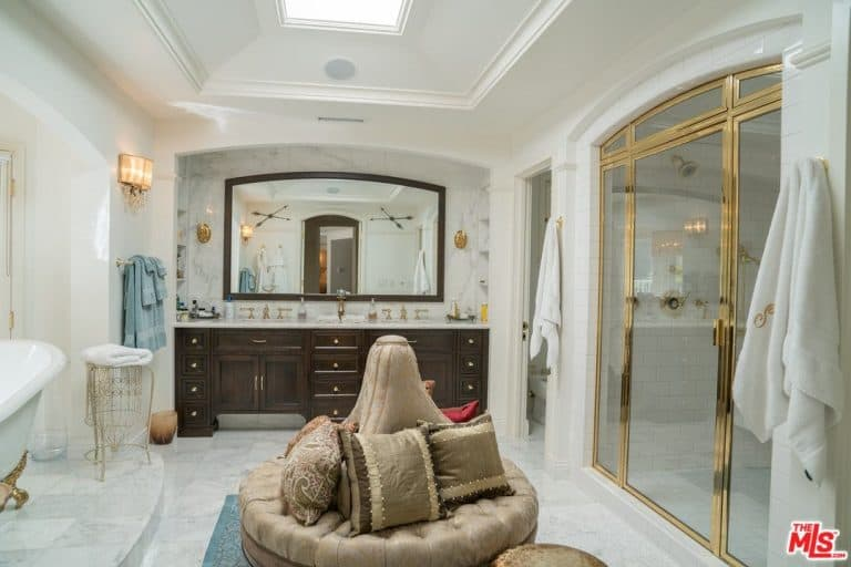 A round tufted seating takes the central space of this elegant master bathroom.