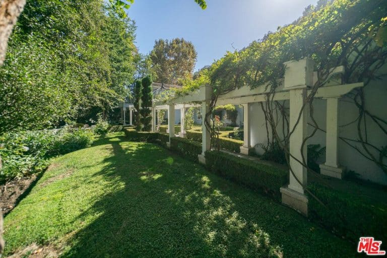 This pergola surrounded by large vines and greens makes the perfect walkway in this gorgeous mansion.