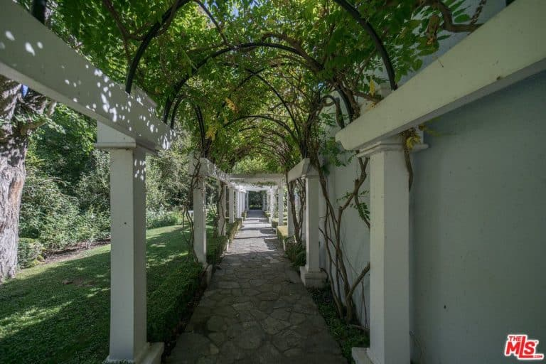 The vine-covered colonnade emphasizes the lush outdoors.