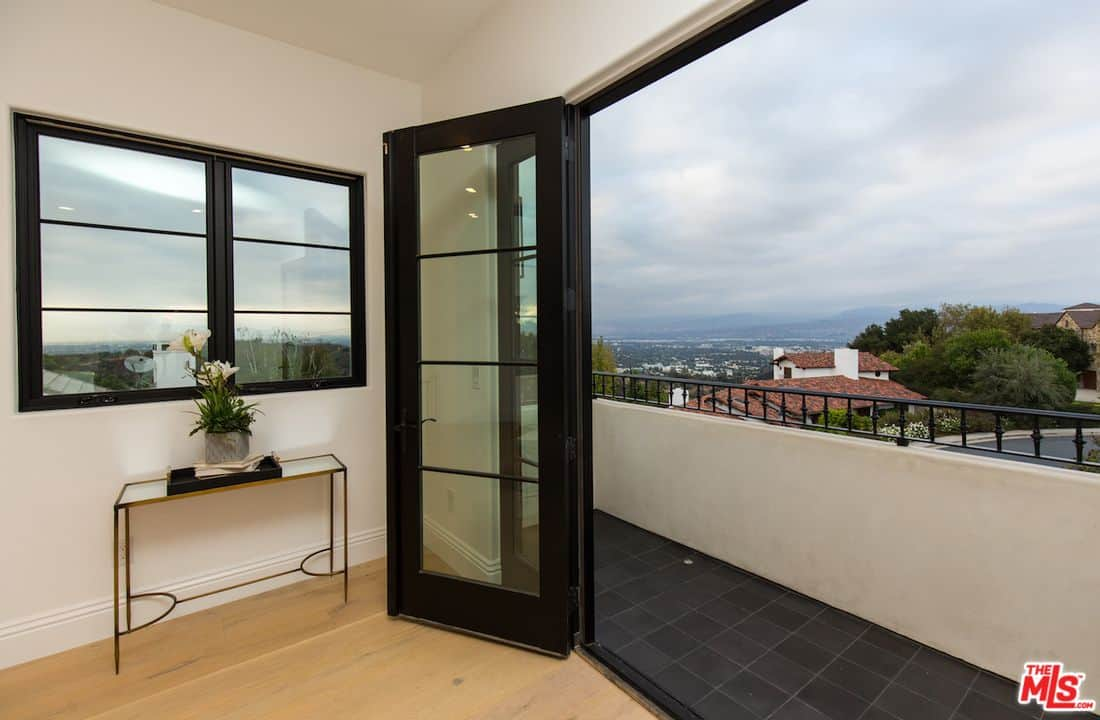A view of Serena Williams' top floor balcony in black tiled flooring, a customized black glass door and windows.