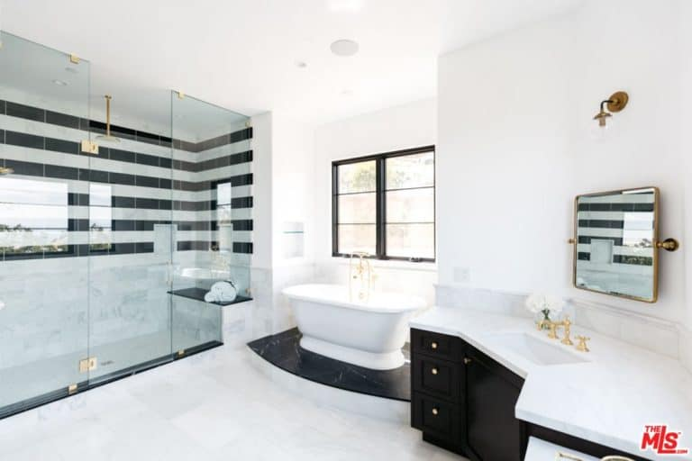 The white walls in the tennis star's bathroom perfectly fits with its huge glass walk-in shower door room and a free standing white bath tub on the corner.