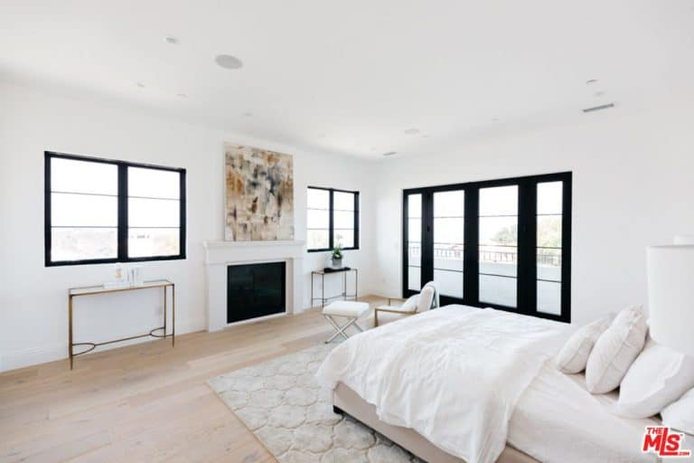 A master bedroom featuring hardwood flooring, white walls and ceiling along with a fireplace and an artistic wall decor.