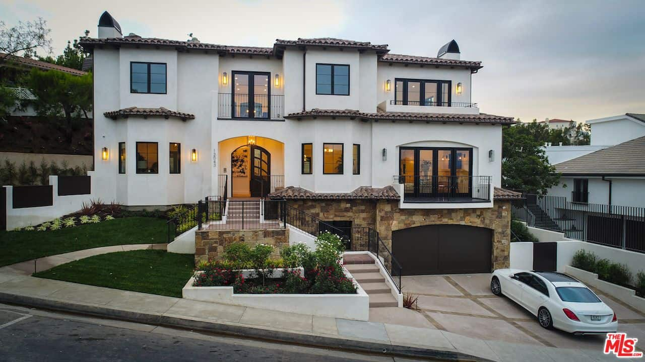 Serena Williams' house front view showcases the stunning white walls, classic black garage, a traditional looking stairway leading to the front entrance along with the nice outdoor landscape.