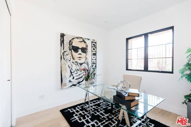 White home office boasts a lovely wall art mounted across the glass top desk paired with a white office chair on a black rug.