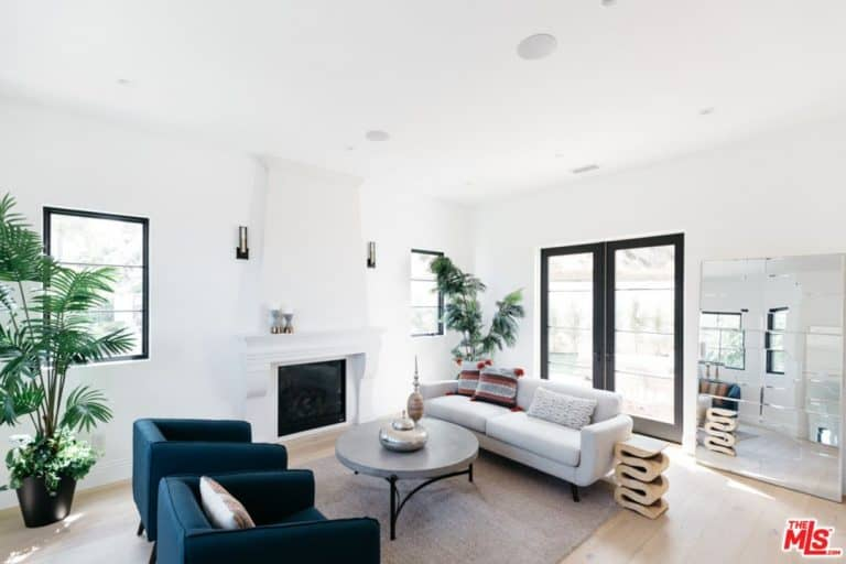 Serena Williams' living room featuring blue and white sofa seating, round gray center table, artsy sofa side table, a large mirror beside the glass door entrance and an electric fireplace for a cozier stay.