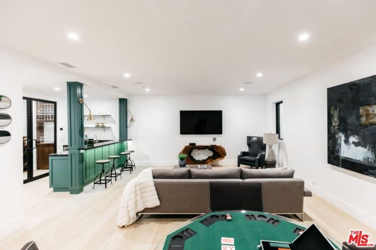 This home features a living space with a cozy sofa set, a bar area with green counter and a game area set on the hardwood flooring of the space.