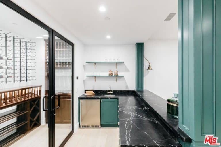 White wine cellar with vertical black racks and wood shelves enclosed in a glass door. It has an L-shaped black marble counter accented with green cabinet, floating shelves and pillars.