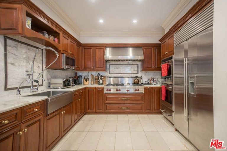 The traditional kitchen has numerous wooden cabinets with gold hardware, marble backsplash and stainless steel appliances.