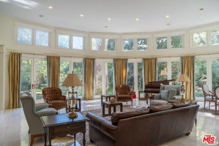 The formal living room looks grand with a tall ceiling emphasized by large windows and tall draperies.