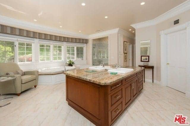 The beige tiles of the flooring is reflected by the beige ceiling and walls. The entire wall by the bathtub area is dominated by a row of white French windows. The sink area stands out against this with its wooden cabinets and drawers.