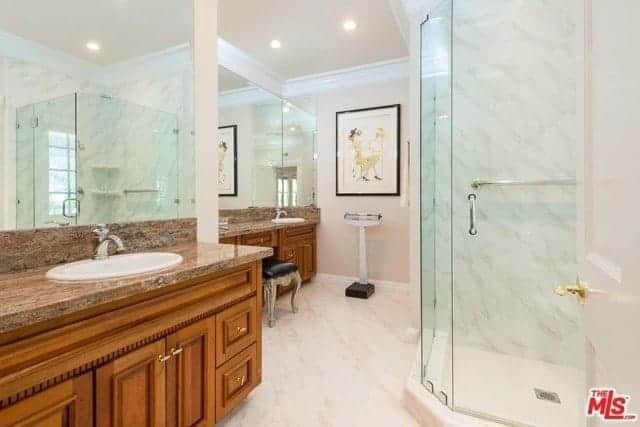 This bathroom maximizes the irregular floor area with two separate vanity areas with its own white sink on brown marble countertops. The elegant wooden drawers and cabinets contrast the beige tiles of the floor and the beige walls adorned with a wall-mounted artwork above the weighing scale.