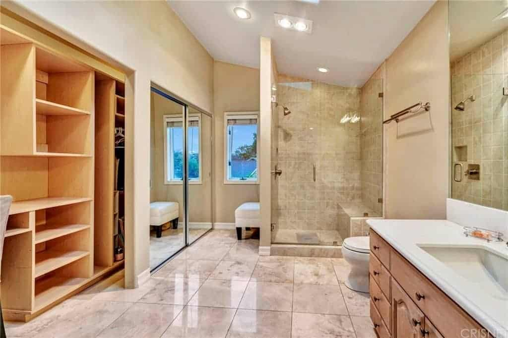 The white shed ceiling of this primary bathroom is paired with beige walls and white marble tiled flooring that makes the wooden vanity stand out as well as the shower area enclosed in glass.