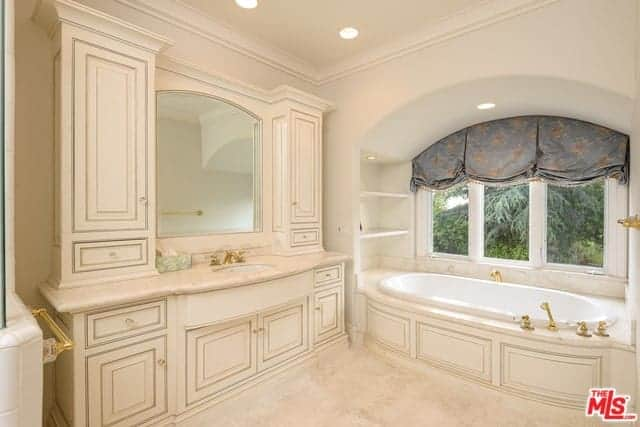 This charming primary bathroom has a light pink hue on its windowed alcove housing the bathtub, the wooden structure of the sink area with cabinets and drawers as well as the pink flooring.