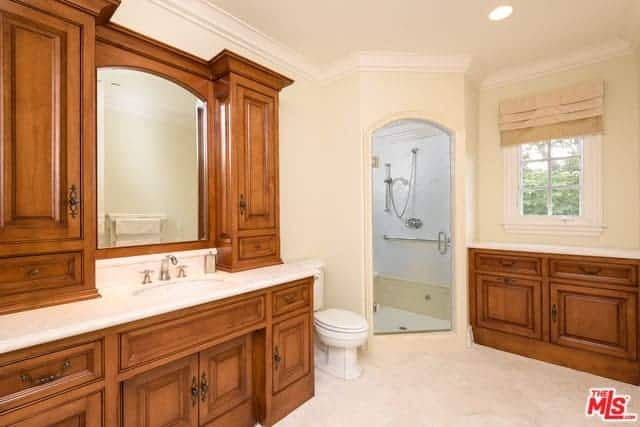 The beige walls, ceiling and floor of this primary bathroom is adorned with the redwood cabinets and drawers of the sink area and vanity area that both have white countertops matching with the white toilet.
