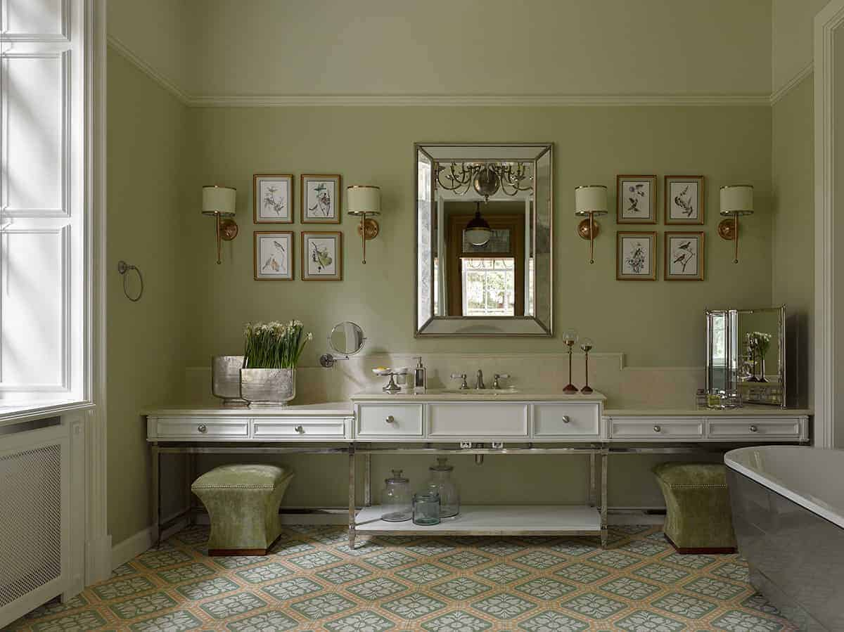 The delightful green and pink patterned floor tiles is a nice complement to the master bedroom that has green walls adorned with framed artworks, wall lamps and a vanity mirror in the middle above the sink area that has drawers.