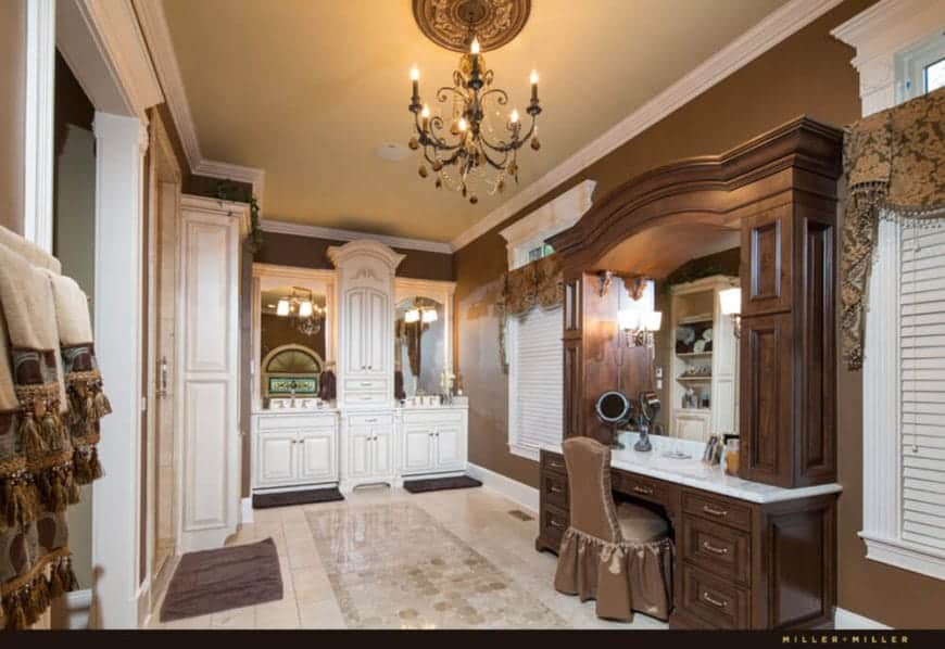The beige ceiling is adorned with a brown chandelier that matches the chocolate brown walls and wooden structure housing the vanity area with built-in drawers and mirror paired with white countertop.
