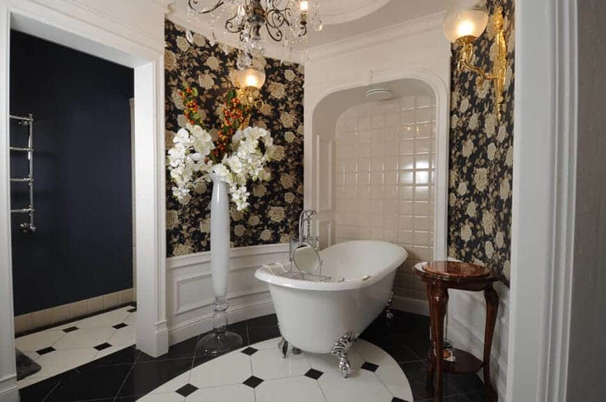 This is a chic bathroom that has walls adorned with floral wallpaper in between white molding and wainscoting contrasted by the black details of the tiled floors.