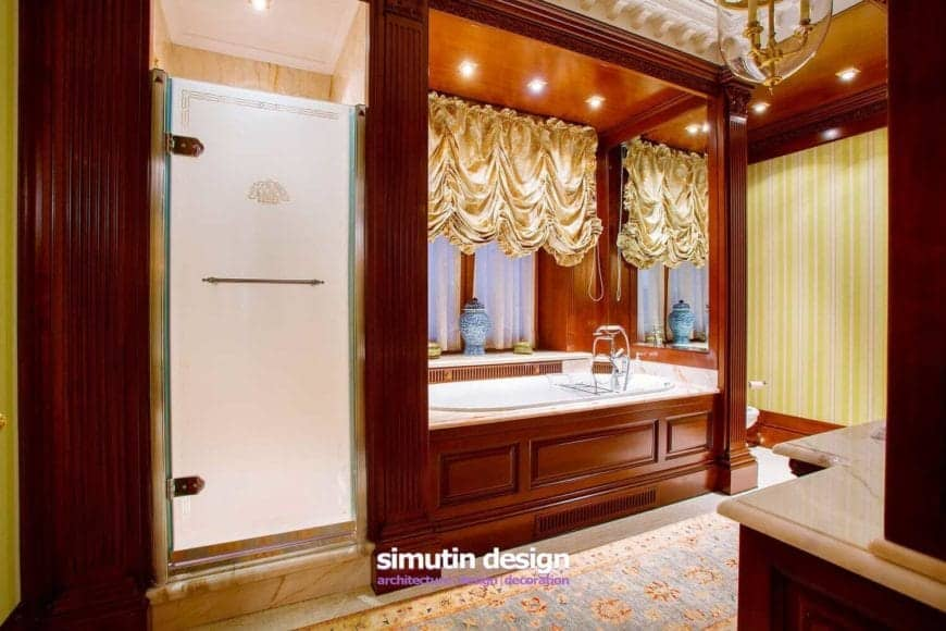 This dramatic and romantic primary bathroom has a wooden alcove that houses the bathtub with mirror and pin light above illuminating the yellow curtain that matches the yellow striped wallpaper.