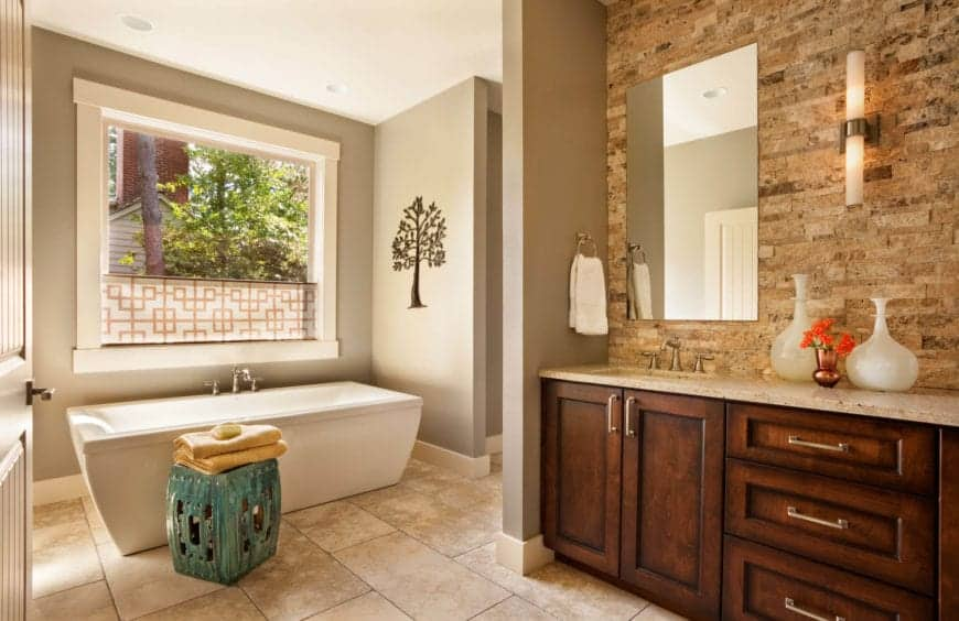 The white freestanding bathtub is placed in a corner of light gray walls with a wide window above and a tree artwork mounted above the head of the tub. The wooden vanity is paired with a wall of tiles that look like wood.