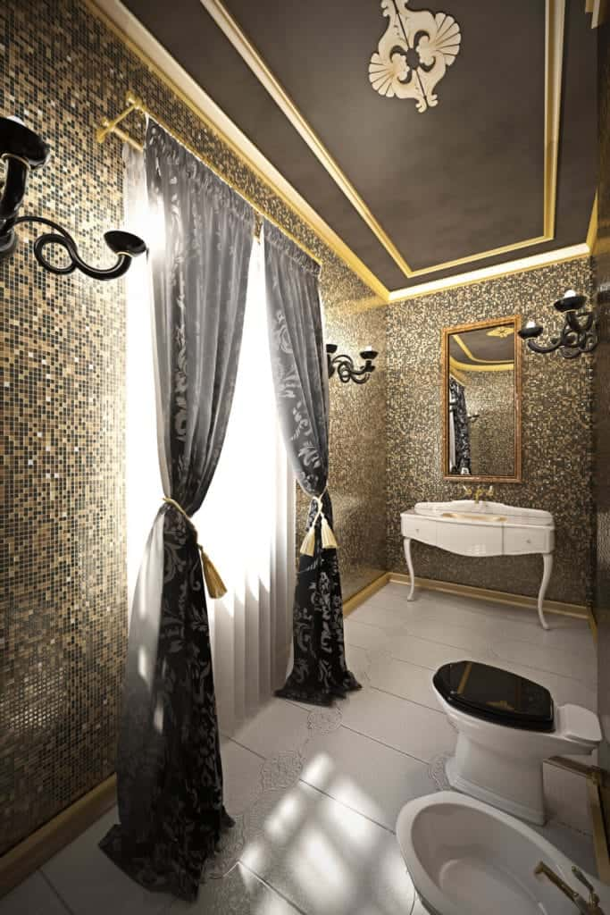 This black bathroom has brilliant gold and black small tiles on the walls adorned with black wall-mounted lamps that match the elegance of the black patterned curtains of the tall window.