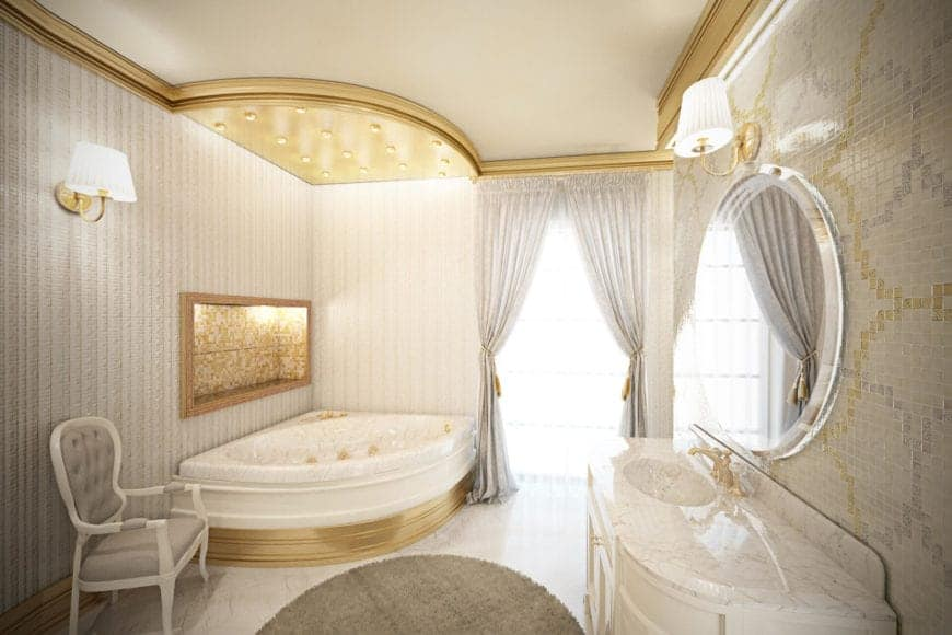 This primary bathroom is a nice fusion of traditional and modern elements. The corner bathtub is adorned with a golden alcove on the gray wall above it and a golden ceiling above it that follows the shape of the tub.