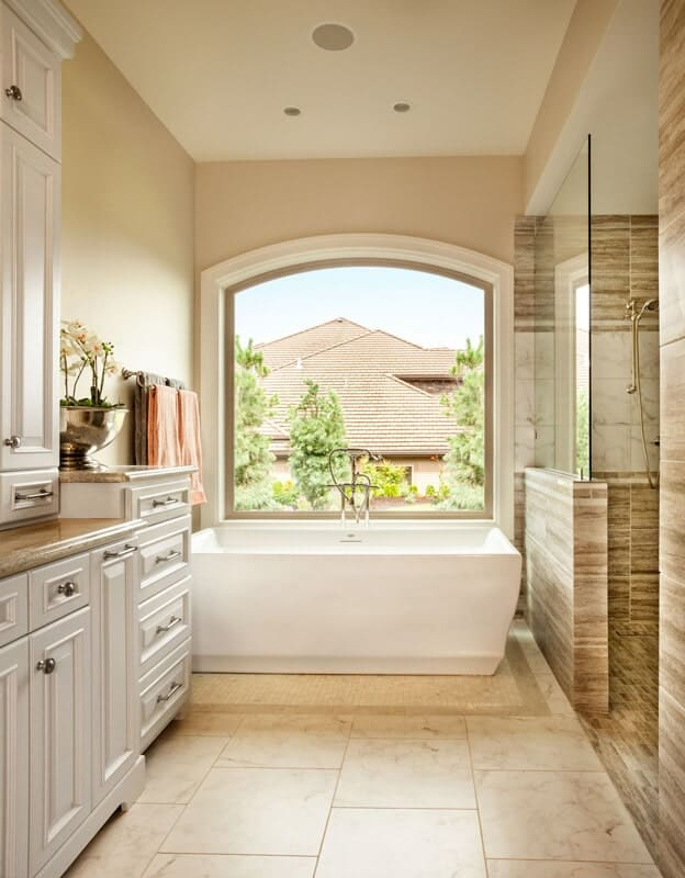 The freestanding bathtub beside the shower area is illuminated by a large arched glass window with a white frame against the beige walls and beige marble flooring.